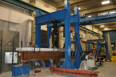 Figure 4. Image of a full-scale fatigue experiment (front left) showing: 1) large-scale steel girder with full depth precast concrete deck panel grouted into place on top of the girder, 2) blue pedestal supporting the end of the steel girder; and 3) two blue load frames, each supporting an actuator.