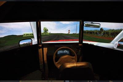 The photo shows the MiniSim, which consists of a quarter-cab setup that includes an adjustable driver's seat, pedals (which are not visible in this image), a steering wheel, and a meter cluster that includes a speedometer. The MiniSim™ has three forward-display LCD televisions. On the far left screen, a simulated side-view mirror is shown. On the far right screen, a simulated rearview mirror is shown. The televisions display a two-lane roadway with yellow lines in the center of the road.  A telephone pole and a road sign on the right side of the road are shown in the center screen. The road sign is not legible in the photo. There are also two trees shown on the left side of the center screen. There is a field of trees in the far right screen and a grassy area with a few trees in the far left screen.