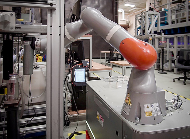 This photograph shows the arm of an industrial robot reaching out with a soil sample in a Shelby tube preparing to insert it into the ESTD.
