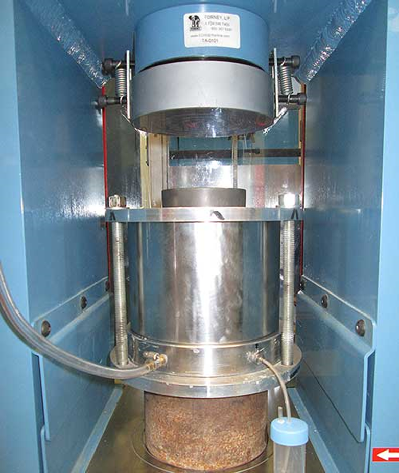 Inside a blue metal chamber, there is a clear cylindrical apparatus with metal cylindrical piece inside of it.