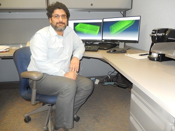 This is a photo of Meysam Mashayekhi, seated at a desk with two computer monitors behind him.
