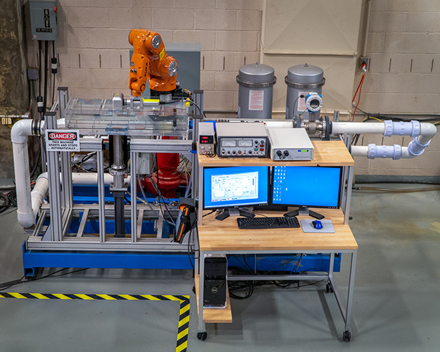 This photograph shows the ex-situ scour testing device, including the rectangular flow channel, the soil sample and hydraulic piston, the industrial robot arm with laser scanner, and computer control system.