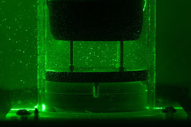The photograph shows a close-up view of the cross-section of the ISTD flow illuminated by the laser. Tracer particles are reflect the laser light and are visible in the flow.