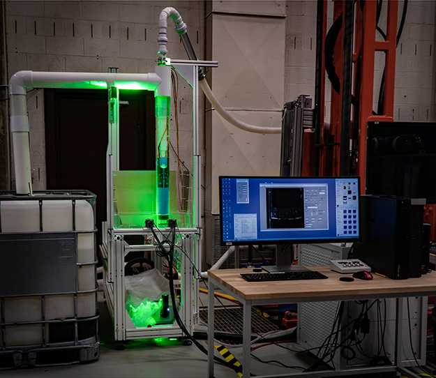 The photograph shows the laboratory ISTD erosion head in clear piping illuminated by the laser, with two cameras mounted in front. In the foreground is the computer controlling the experiment.