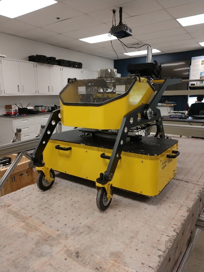 Photo is of the robotic air-coupled acoustic array, which is a large yellow machine on wheels. Photo was taken in a lab.