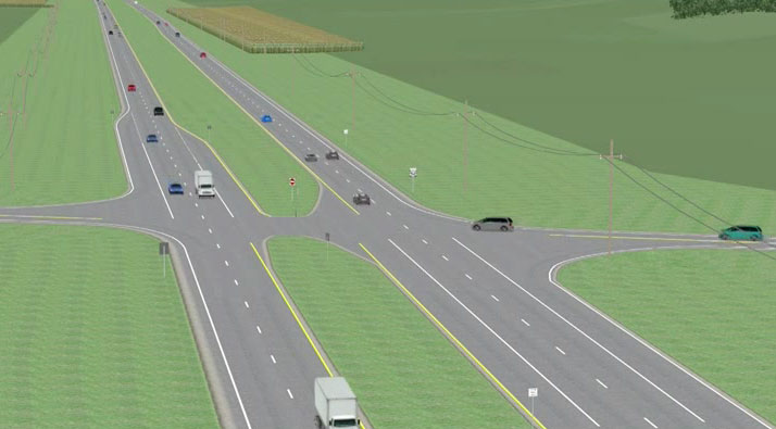 The image is a screenshot from the video. It shows a four-lane roadway (two lanes in each direction) separated by a grassy median. Vehicles are shown on the roadway.