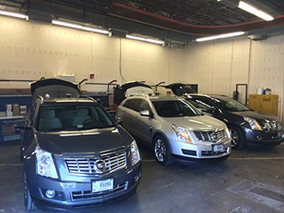 Figure 2: This photograph shows three side-by-side Cadillac sport utility vehicles in the Vehicle Preparation Garage at the Turner-Fairbank Highway Research Center.