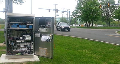 Figure 3: This photograph shows a sport utility vehicle traveling through a connected intersection at the Turner-Fairbank Highway Research Center. Above the vehicle are two traffic lights on an overhead polesignal mast arm. To the left of the vehicle is a traffic control cabinet with the door open, showing computerstraffic signal controllers and equipment inside the cabinet.