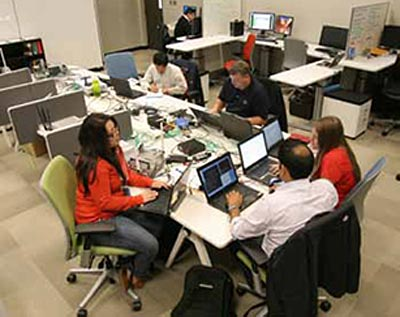 Figure 4: This photograph shows six individuals in a work center sitting at their workstations. Three people near the front of the photo are working together on laptop computers. Three other people are working individually behind them at different workstations.