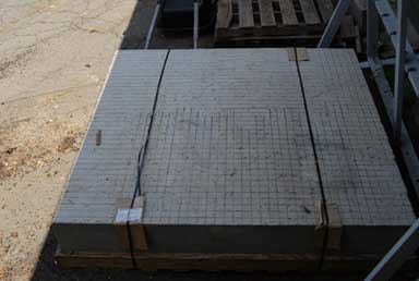 A rectangular slab is viewed from an overhead angle. The surface of the slab has been scored with lines forming a grid. The concrete slab is secured to a wooden pallet with wire bands and cardboard has been inserted between the wire bands and the concrete to prevent damage to the slab.