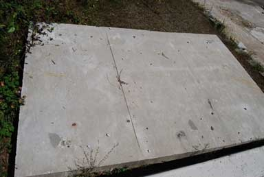 A rectangular piece of concrete lying flat on a grassy/dirt area is displayed. One third of the concrete piece has a vertical scoring line.