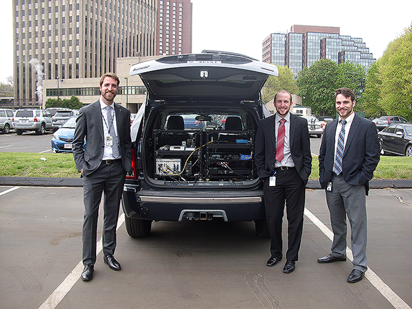 Photograph. Instrumented research vehicle (IRV) used to collect data through work zones with Taylor Lochrane (left) from FHWA, Christopher Melson (center) from FHWA, and Andrew Berthaume (right) from the Volpe Center. The back of a blue 2007 Jeep Grand Cherokee is open, showing electronic data collection equipment installed on black metal brackets. Three young gentlemen in suites and ties pose around the Jeep. The Jeep is stationed in a parking lot, in an urban setting with surrounding brick buildings.