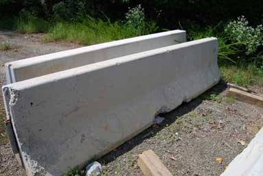 Two 3-ft high concrete barriers are viewed from a side angle. The barriers are parallel and upright with approximately 1 ft of space between their sides. The bottom surfaces of the barriers are in contact with the ground. The barrier in the foreground has suffered damage in its upper left corner and in two locations on its bottom edge. In addition, the left portion of the barrier exhibits severe abrasion.