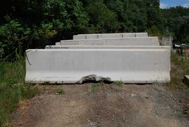 Six concrete barriers of various shapes and sizes are lined up in an upright position on a dirt/gravel patch. The barriers The two front barriers are of similar size and shape, approximately 3-ft tall and 12-ft long. Halfway along the bottom edge of the front barrier, significant chipping damage is displayed. A faint grid pattern can be seen along the length of the barrier.
