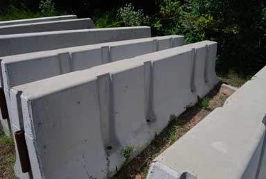 Six concrete barriers are viewed from a side angle. The barriers are in and upright, standing position, and are roughly parallel. The three barriers shown from the far right to middle screen are designed with four vertical channels. End fasteners can be seen on two of the three barriers. At the bottom of each channel is a vertical hole that is used to bolt the barrier into place.
