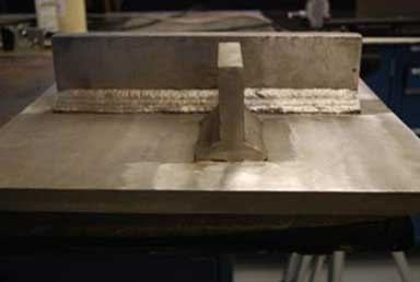 The photograph consists of a large metal surface showing two smaller rectangular metal plates that have been welded in place. The longer metal plate is horizontally positioned in the photograph, with the shorter metal plate placed perpendicularly. The welds joining the edges of the smaller plate to the rectangular surface are clearly visible.