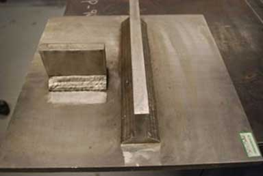 The photograph consists of a large metal surface showing two smaller rectangular metal plates that have been welded in place. The shorter metal plate is horizontally positioned in the photograph, with the longer metal plate placed perpendicularly. There is a significant gap between the two perpendicular pieces. The welds joining the edges of the larger plate to the rectangular surface are clearly visible.