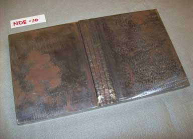 The photograph is an overhead view of two rectangular plates joined with a butt-weld to create a larger rectangular plate. Some corrosion is present in the welded plates. The specimen is labeled NDE-10.