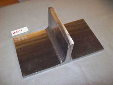 The photograph is an angled overhead view of two polished rectangular plates joined with a T-weld. The larger plate is resting flat on a surface and the smaller plate is perpendicular. The specimen is labeled NDE-13.
