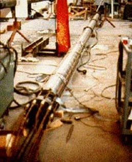 This photo shows a pipe pile lying down with laboratory instrumentation around the perimeter. Wiring is displayed across the floor and pile, with miscellaneous items around the laboratory.