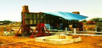 This photo displays a reaction frame assembly for load testing of model spread footings in a field environment. A separate concrete square footing is shown in the foreground.