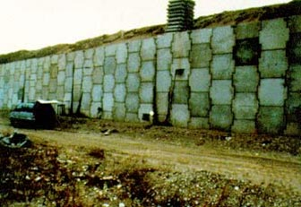 This photo depicts the front of a cruciform panel-faced mechanically stabilized earth (MSE) wall with a small backslope.