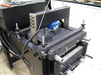 This is a photo that shows a large-scale direct shear device under operation. The bottom box is displacement allowing some of the aggregate being tested to show in the figure.