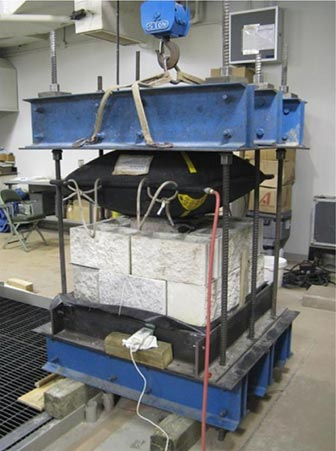 This is a photo showing a calibration reaction assembly with two courses of concrete masonry blocks stacked up and an inflated airbag pressed against them from the top.