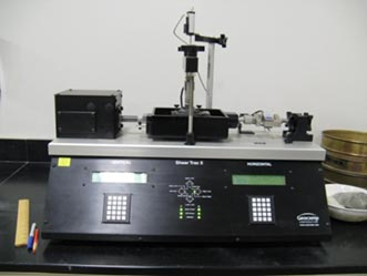 This is a photo showing a front view of a standard direct shear device. There are controllers on the bottom with the shear box on the top, connected to a motor and a load cell.