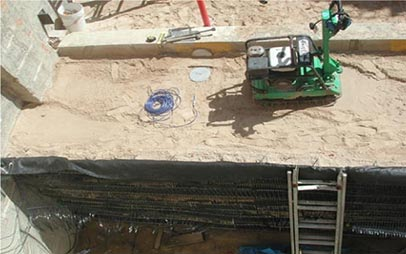 Top-down view showing into the outdoor geotechnical sand pits. A mechanically stabilized earth (MSE) shoring wall is on one side and a green lightweight vibratory compactor is shown on top of the sand.