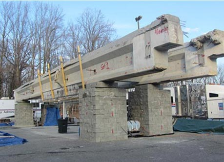This photo shows four GRS piers with concrete masonry units (CMUs) on a concrete pad. Two large concrete I-beams are positioned on top of the GRS piers.  The beams have salt spray catch barriers attached to them.