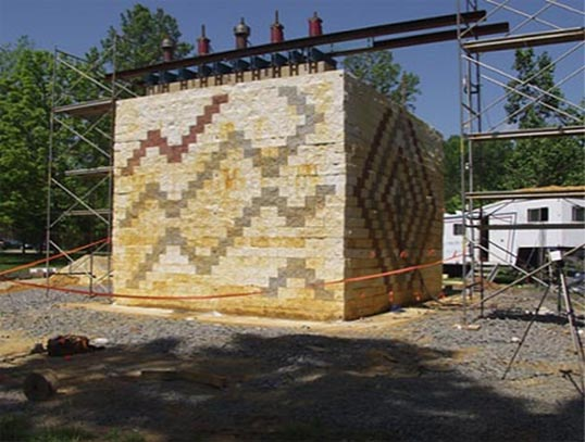 This photo shows a GRS abutment experiment built with a concrete masonry units (CMU) facing element on the outdoor strong floor. The CMU blocks have a zigzag pattern in different colors.  A concrete footing is positioned on top near the edge of the face of the GRS abutment with five hollow core hydraulic jacks on top. The hydraulic jacks are connected to load cells. Scaffolding flanks both sides of the GRS abutment experiment and reference beams are supported on the scaffolding to measure vertical deformations.