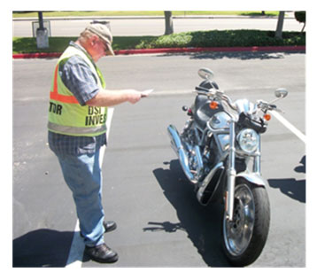 The image shows a control stop investigator standing in a parking lot next to a parked motorcycle. He is holding a checklist and performing an inspection of a motorcycle belonging to a control participant.