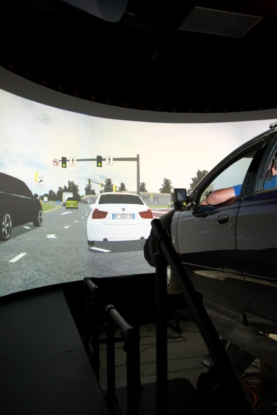 This image shows the current highway driving simulator, a car attached to a moving platform, in front of a panoramic video screen.