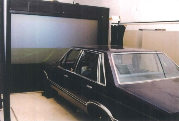 This image shows an early highway driving simulator, with a stationary car in front of a video screen.
