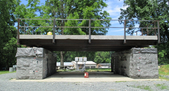 Figure 11. Photo. Virginia pilot bridge slab test bed at TFHRC. The photo shows a large portion of the bridge deck from the Virginia pilot bridge. The slabs are horizontal across the photo. The slabs rest on top of two large concrete block piers situated at each end of the slabs. The slab has rails around it for the safety of workers.