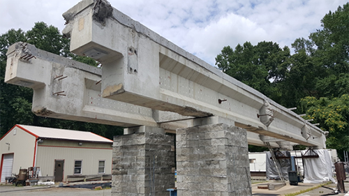 Figure 12. Photo. Two AASHTO prestressed concrete girders at TFHRC. The photo shows a front-side view of two prestressed concrete girders. Each girder is resting on two concrete block piers.