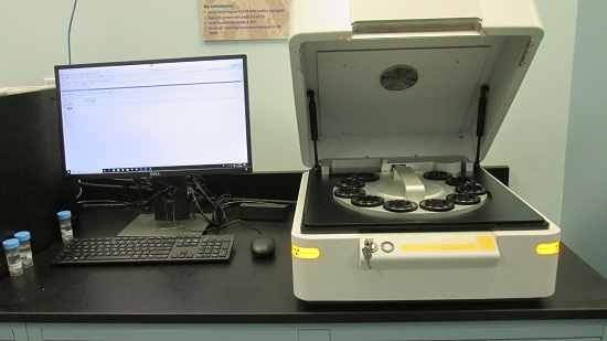 The image shows the x-ray flourescence spectroscopy machine on the right, and a computer and monitor on the left.