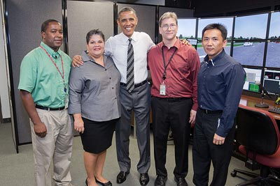 President Obama poses for a picture with (from left to right) Curtis Morrisette (onsite contract support), Monique Evans (Director, Office of Safety R&D), Jason Williams (onsite contract support), and David Yang (Human Factors Team Leader).