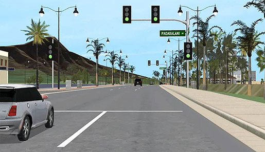 This  image shows an in-vehicle view of someone driving down a road toward Diamond  Head, Honolulu.  To the left and right  side are many trees. A large volcano is visible to the left. There is also a vehicle  nearby to the left and vehicles ahead in the distance.