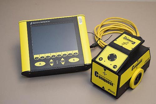 A small two wheeled yellow vehicle-like device is attached by a cable to a yellow rectangular instrument with a display screen.