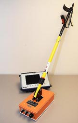 The right photograph is an orange rectangular instrument with a long yellow handle extending diagonally upward to the right. The rectangular device from the left image is to the rear of the long handled instrument.