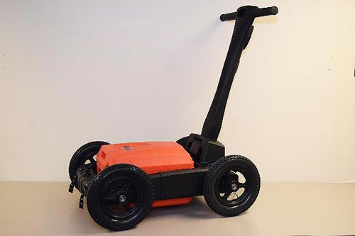 This figure is a photograph of a four-wheeled cart with a central orange box. A black handle extends from the right end of the cart diagonally upward to the right.