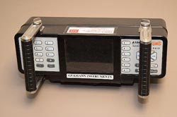 This figure consists of two photographs. A control and recording rectangular instrument is in the left photograph. It has a central display screen with control panels on either side. Two handles placed over the control panels extend from the instrument into the foreground.