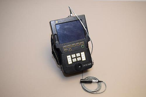 The small black instrument is roughly rectangular with a display screen on the upper half and a small keypad on the lower half. A cable is plugged into the top and in the foreground the cable is connected to a small probe. A rear-mounted hand strap can be seen in the photo.