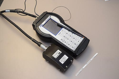 This photograph consists of two devices. The top device is a hand-held instrument with a small display screen on the upper third of the device and a key pad on remaining device face. The instrument is connected by a cable to a small black box.