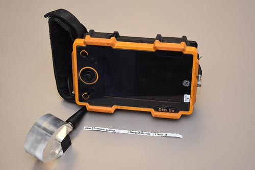 The black instrument is rectangular with an orange frame and consists of a viewing screen with three control buttons. A hand strap is affixed to the left side. A clear plastic probe is positioned in the foreground, with a cable that connects to the left rear of the orange/black device.