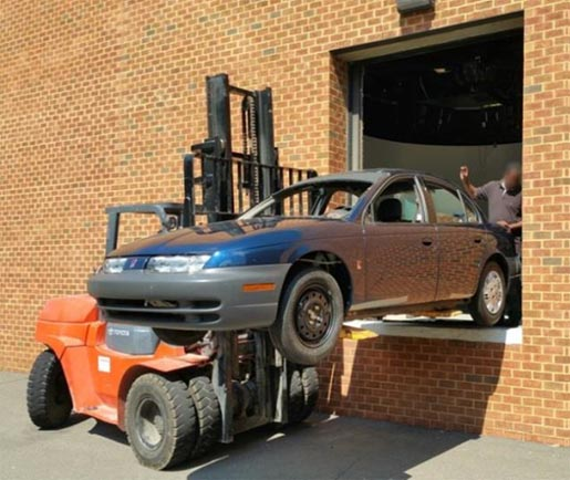 This image shows an old sedan being removed by a forklift from a large laboratory door.