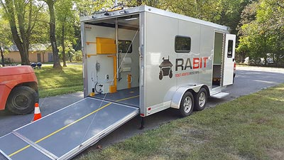 The  photo shows a large silver trailer with its rear door open. There is a ramp extending  from the trailer floor down to the ground that allows the RABIT-CE™ bridge deck  assessment tool to ride down to the surface being tested.
