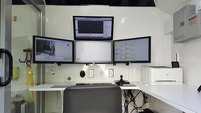 The photo shows the inside of the trailer. There is a desk and chair, with four display monitors mounted on the wall.